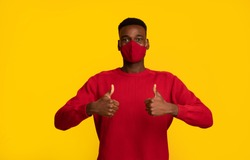 Happy black guy in red protective face mask showing thumbs up at camera, posing isolated on yellow background, african american man support social-distancing during coronavirus pandemic, copy space