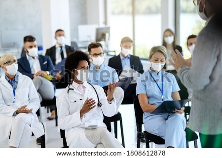 Happy black healthcare worker wearing protective face mask communicating with a businessman who is holding educational event at convention center.  Photo stock ©