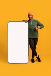 Happy Black Hipster Guy Leaning At Big Smartphone With Blank White Screen And Gesturing Thumb Up, Cheerful African Man Recommending New App Or Website, Standing On Yellow Background, Mockup Image
