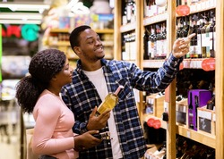 Happy black man and his girlfriend buying wine at liquor department of supermarket. Lovely African American couple shopping for alcoholic drinks at huge mall together