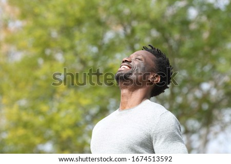 Happy black man breathing deeply fresh air in a park with a green tree in the background a sunny day