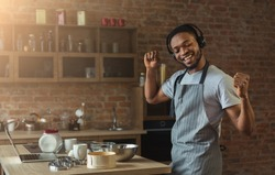 Happy black man in earphones listening to music and dancing while baking in kitchen