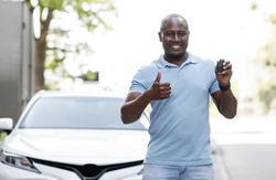 Happy black man showing automatic car key and thumb up, standing by nice white auto outdoors. Cheerful african american driver buying automobile, recommending auto salon or leasing service, copy space