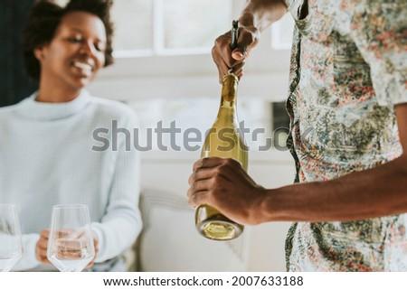 Happy black man uncorking a wine bottle Stock photo ©