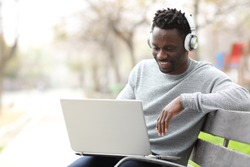 Happy black man watching media on laptop wearing headphones sitting on a bench in a park