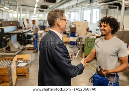 Happy black manual worker shaking hands with company engineer in at  factory plant.