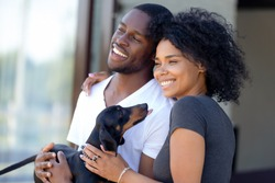 Happy black millennial couple hugging standing outdoors holding dachshund puppy, childfree spouses enjoy time together having fun with dog looks away shooting outside, family with pet portrait concept