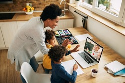 Happy black mother and kids waving to a teacher while having video call over a computer from home.