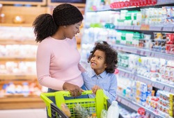 Happy black mother with her daughter shopping for groceries, selecting dairy products at mall. Young African American family with trolley buying food at huge hypermarket