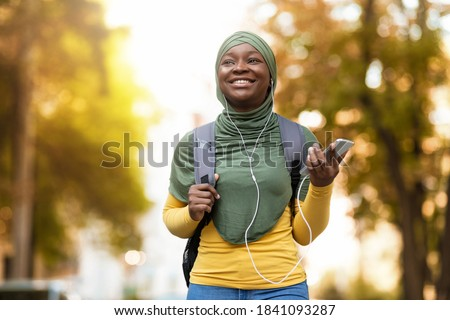Happy black muslim woman in hijab listening music with smartphone and earphones outdoors, african islamic female student enjoying favorite songs while walking by street with backpack, free space Stock fotó ©