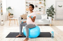 Happy black pregnant woman working out with dumbbells on fitball at home. Positive expectant African American lady doing strength exercises, keeping in good shape while waiting for baby