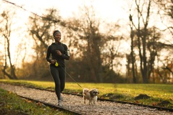 Happy black sportswoman running with her dog at the park.