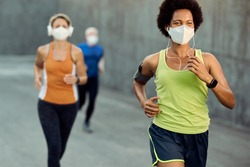 Happy black sportswoman wearing protective face mask while running outdoors during COVID-19 epidemic. There are people in the background.