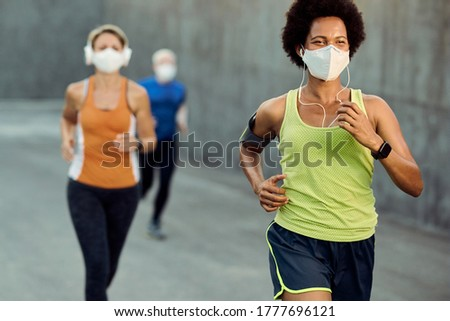 Happy black sportswoman wearing protective face mask while running outdoors during COVID-19 epidemic. There are people in the background.  Foto stock ©