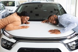 Happy Black Spouses Hugging Hood Of Their New Car In Dealership Office, Overjoyed African American Couple Leaning At Surface Of Luxury Automobile, Enjoying New Family Vehicle, Closeup Shot