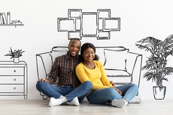 Happy Black Spouses Imagining Interior Of Their New Flat, Sitting On Floor Near White Wall With Doodle Drawings, Young African American Couple Planning Relocation, Creative Collage
