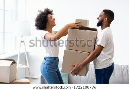 Happy Black Spouses Packing Boxes For Moving, Relocating To New Apartment Standing At Home. Real Estate Rent, Mortgage And Ownership Concept. Family Preparing To Move House.
