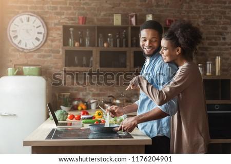 Happy black wife hugging husband while making salad in loft kitchen