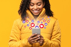 Happy Black Woman Holding Smartphone With Hearts And Like Buttons Standing On Yellow Studio Background. Phone User Networking Online Using Social Media, Reading Feed News, Commenting And Sharing Posts