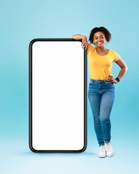 Happy black woman leaning on big smartphone with blank white screen, smiling at camera on blue studio background, mockup for mobile app, website, your advertisement design