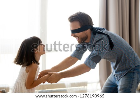 Happy blindfolded father playing hide and seek active game catching excited little kid daughter at home, dad and joyful child girl having fun enjoy weekend in living room spending free time together