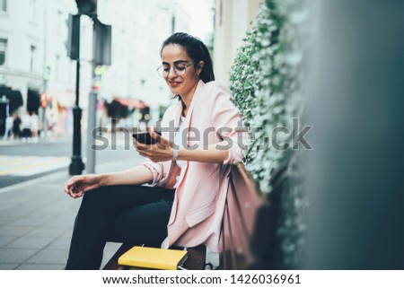 Happy blogger making payment online on smartphone device via 4G internet resting on bench outdoors, successful young woman in stylish jacket and glasses messaging in friendly chat on mobile phone