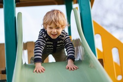 Happy blond boy having fun and sliding on outdoor playground.