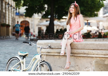 Happy blond-brown girl smiling and sitting on a fountain. Wearing pink head wrap and dress with a pattern of flowers. With retro bicycle nearby. In the old European city.