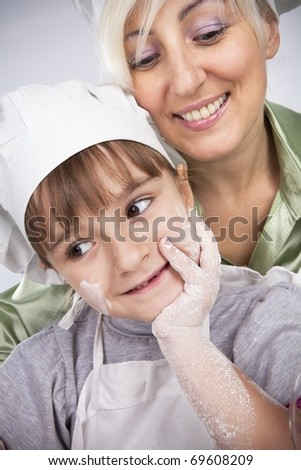 Happy, blond caucasian mother and daughter coocking