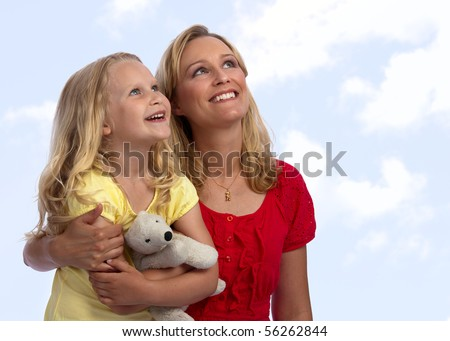 Happy, blond caucasian mother and daughter hugging and looking up into the sky