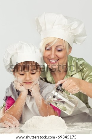 Happy blond caucasian mother and daughter preparing dough and having fun