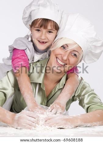 Happy, blond caucasian mother and daughter preparing dough and having fun