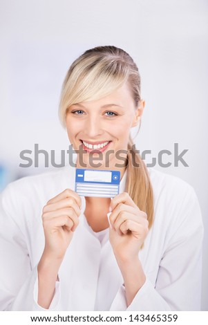 Happy blond doctor showing health card in a close up shot
