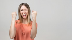 Happy blond girl clench fists and shouting yes, celebrating victory, achieve goal. Human emotions, facial expression concept. Studio shot, gray background. Place for ad