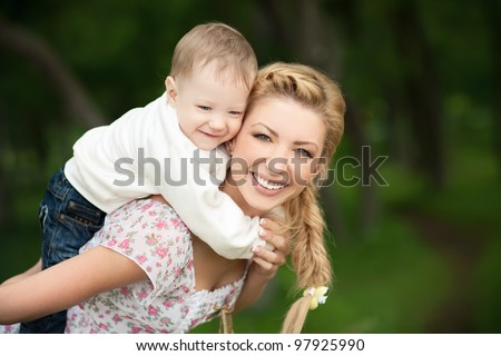happy blond mom with her little son enjoying nature on a background of green leaves. Much of copyspace