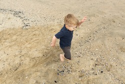 Happy Blond Toddler Boy Runs Across Sandy Pebbled Beach in Bare Feet
