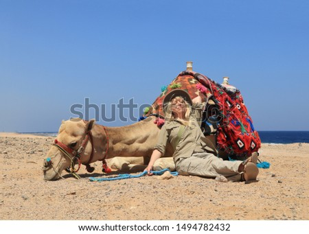 happy blond woman resting next to her camel in the desert