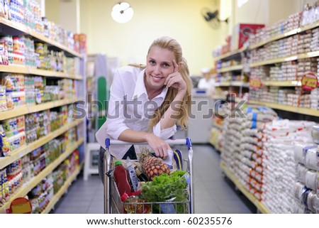 Happy blond woman shopping in the supermarket