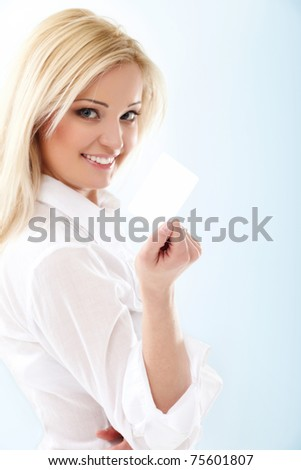 Happy blond woman showing blank credit card. Focus on card.