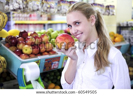 Happy blond woman smelling a mango in the supermarket
