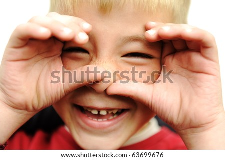Happy blonde boy closeup, smiling, laughing, very happy with hands on his face - stock photo