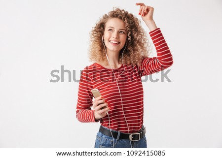Happy blonde curly woman in casual clothes and earphones listening music by smartphone while looking away over grey background