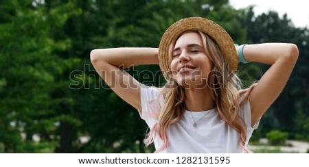 Happy blonde girl in straw hat on a holiday in the park.  Relaxation, recreation. Smile, emotion, state of mind