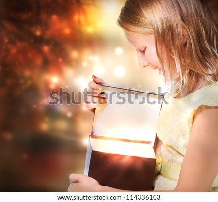 Happy Blonde Girl Opening a Present Box