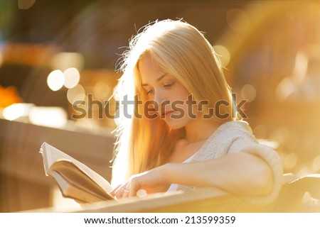 Happy blonde girl sitting and reading a book