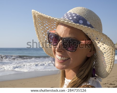 happy blonde girl smiling portrait in the beach  wearing hat and sunglasses, summer holidays