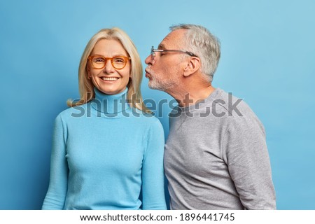 Happy blonde middle aged woman gets kiss in cheek from beloved husband. Senior couple have romantic relationship in old age. Affectionate male pensioner kisses wife stand indoor over blue wall