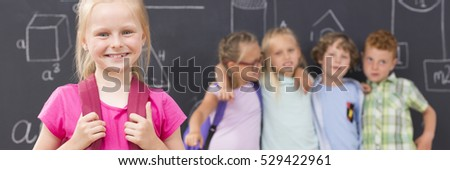 Happy blonde school girl, in the background group of her friends, panorama