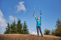 Happy blonde triumphantly raising her hands holding trekking sticks after she climbed on stone top of hill, on the background of several green trees and beautiful blue sky.