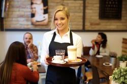 Happy blonde waitress holding tray, smiling.